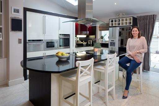 Gina Cassidy in her kitchen with its high-gloss units and black granite island. As well as a hob, the island houses a barbecue, ideal for family summer parties. Photo: Tony Gavin