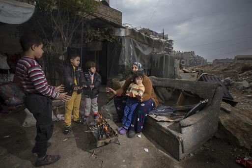 A family try to stay warm in the Saif Al-Dawla, part of East Aleppo. Photo: Mark Condren