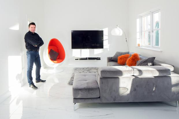 Snooker coach Fin Ruane in one of the two family living areas. The grey and white colour scheme is enlivened with touches of red