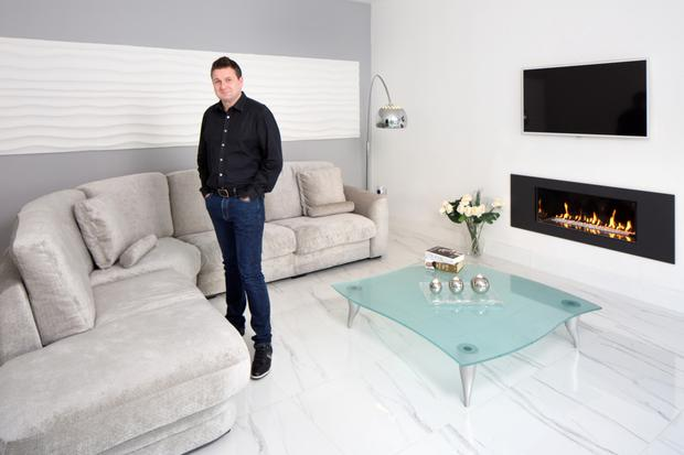 Fin in the other livingroom, which, like most of the living areas including the hall and kitchen, is floored in porcelain. The fire is gas, the curved light was brought by a friend from Saudi Arabia, while Fin made the plaster piece behind the sofa himself