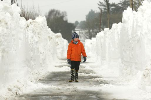 White-out: Seven-year-old Brian O'Rourke from Garryhill, Co Carlow looks up at the top of the snow drifts. Photo: Finbarr O'Rourke