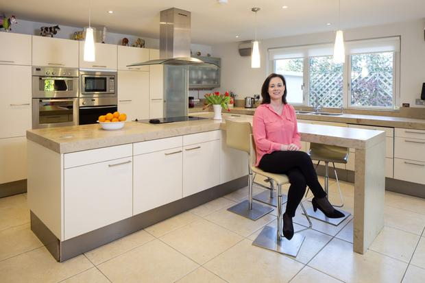 Dentist Aisling O'Mahony in her kitchen with its L-shaped island and limestone worktop. Aisling's four kids can cook, which is just as well, as she says she herself is no Rachel Allen.