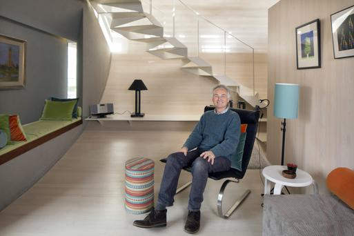 Joe Kearney in his living room on the middle floor. There are no ceiling lights, only lamps and concealed lighting. All the soft furnishings were made by Sally, Joe's friend and companion of many years