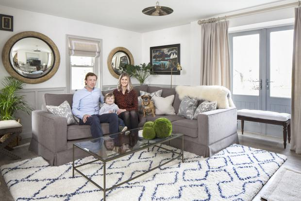 Cathal and Geri with their three-year-old son, Finlay, and Baxter, their pugalier - a cross between a pug and a Cavalier King Charles — in their spacious living room, which is furnished in a muted palette. The two mirrors are antiques and have slightly misty glass.