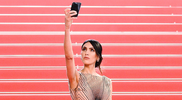 Selfie harm: A guest at the Cannes Film Festival takes a photo of herself. Photo: Getty Images