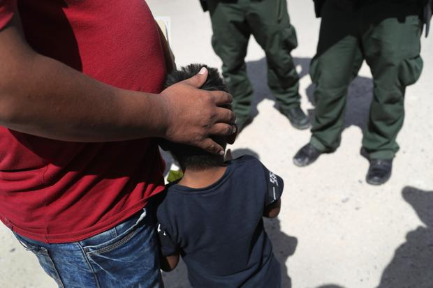 Crisis: A father and son from Honduras are taken into custody at the US border with Mexico