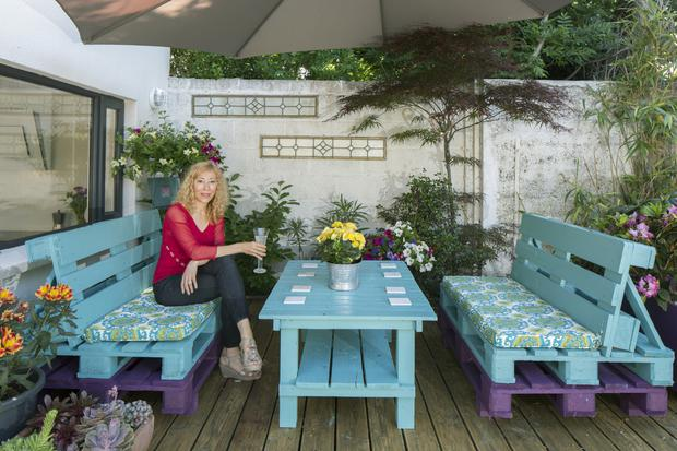 Dance teacher Mariam Ribom on her patio with its colourful furniture made from pallets and painted. The house had virtually no garden originally, but they were able to buy a strip of ground to enlarge it. Photo: Tony Gavin