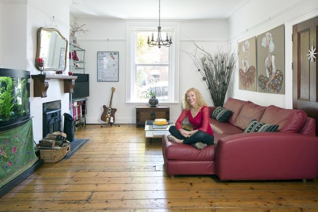 Dance teacher Mariam Ribon in her delightful living room, which she has decorated simply with white walls and stripped-back floorboards. The diptych on the wall behind the sofa is by Mariam's sister. Her tropical fish are in the tank, and below it, screened by a colourful piece of fabric, are the workings of the tank