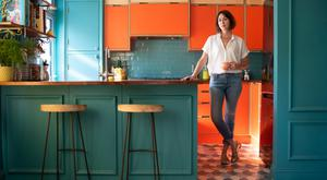 Gillian Hyland in her mid-century-modern-style kitchen. The units are birch plywood, with orange formica doors. Gillian sourced and bought every item herself, including the fish-scale floor tiles, and the glass lamps, which she bought in John Lewis. The bevelled glass of the lamps matches that of the glass units above the formica cupboards