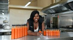 Ellie Kisyombe with her Our Table hot sauces which are now on sale in the Good Food Store. Photo: Caroline Quinn