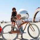 Barbara and Romi explore Burning Man on a bike with a trailer