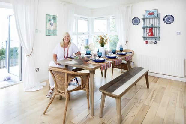 Lorraine in the dining area of her open-plan living room. She and Michael repaired all the existing windows. The tables and benches were bought in a local furniture shop, Michael Murphy of Wexford