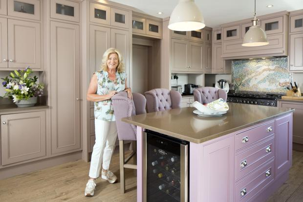 Maria Nolan in the kitchen, which was designed and made by Bernard Vaughan of Ennistymon. The units are painted a neutral shade, while the island is a contrasting bubblegum pink. The floor is made of timber-effect floor tiles, and the wall mosaic is by Maria, who is very artistic