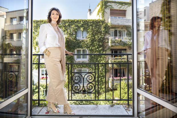 Helen on the balcony of her apartment in Neuilly; it's a salubrious part of Paris with chic restaurants nearby. However, she chose it for its proximity to the Bois de Boulogne. Photo: Tony Gavin