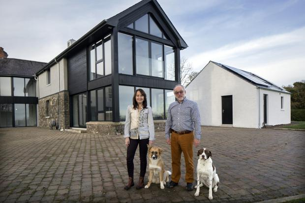Tim and Mairead Andrew with their dogs, Blaze and Nelson, outside their home, which is a combination of 21st-Century design and 19th-Century period detail