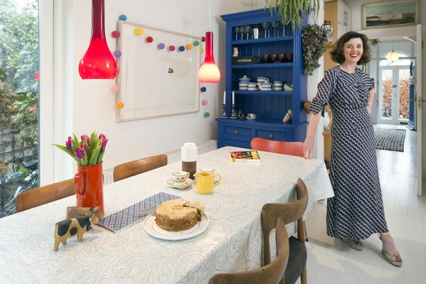 Solicitor Bernadette Parte in the dining secion of her kitchen. She loves blue and collects Cornish blue ware for her dresser, which she had made for the space. The red lights are Murano glass. Photo: Tony Gavin