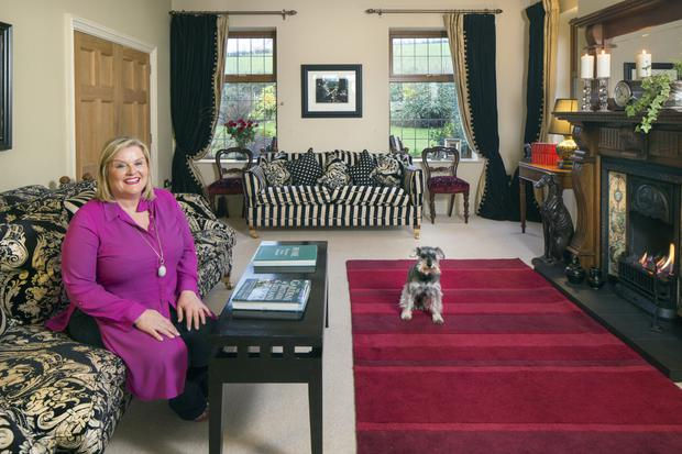 Joyce with Murphy, her adorable miniature schnauzer, in the living room of her lovely home. She also has five cats.