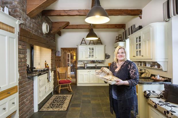 Joyce Brownless in her country-style farmhouse kitchen complete with a four-oven Aga and three Gaggenau ovens. The upholstered window seat is for the guests.