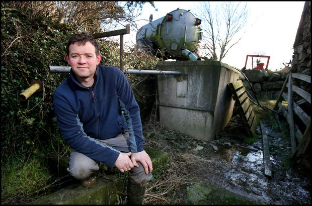Dairy farmer Shane O'Loughlin from Aughrim Co Wicklow at the resevoir tank leading from his spring. Photo: Steve Humphreys