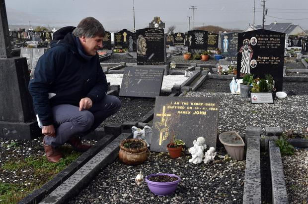Tragedy: Kim Bielenberg at the grave of 'Baby John'. An earlier gravestone was destroyed. Photo: Don MacMonagle