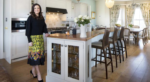 Award-winning entrepreneur Ramona Nicholas in her painted country-style kitchen designed by Greenhill Kitchens. The worktops are marble, while the island top is walnut. Photo: Tony Gavin
