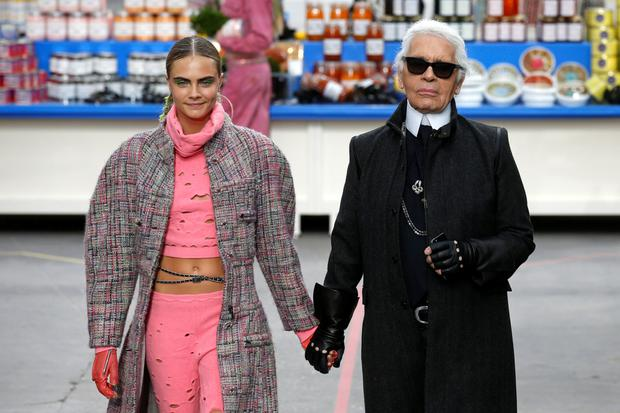 Supermodel Karla Delevingne walks with Karl in March 2014 in his supermarket-themed show where shelves were stocked with Chanel-branded pasta, washing powder and vodka