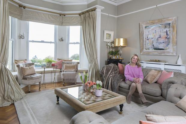 Darbhaile in one of her two bay-windowed reception rooms. She has decorated it in muted tones, with pops of pink and gold