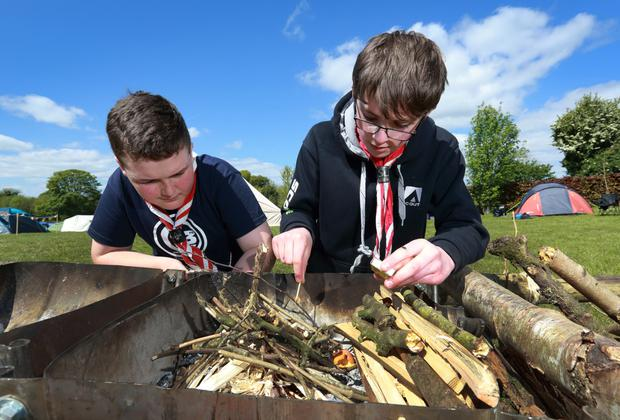 Striking out: Cian Casey (Cubs) and Cian O'Donnell (Scout) light a camp fire. Picture by Frank McGrath