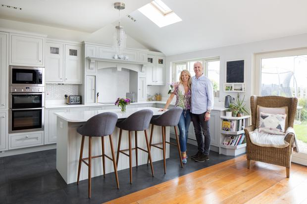 Niall and Lisa in their country-style kitchen, which is painted in Farrow & Ball's Pavilion Grey, chosen by Lisa, who has a great eye for colour. The kitchen is full of light, just like the rest of the house. The level of light is one of the benefits of the new-build - it's particularly important for Lisa's work as an artist. Photo: Tony Gavin