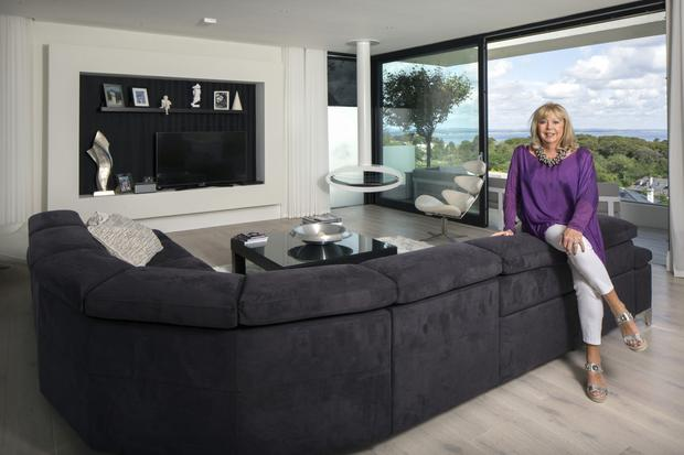Interior designer Liz Balbirnie of Habu Interiors in her magnificent monochrome living room. She felt the decor needed no colour, as vibrant greens and blues are provided by the vista outside. The space-age-style oval hanging from the pipe is a stove