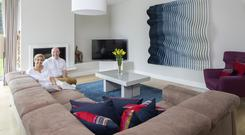 Val and Karl in the living room. The floor is engineered oak, while the coffee-coloured seating unit is from DFS. Karl felt the wall needed something special, and designed the blue wavy sculpture with the help of Fergal O'Leary of Horizon Furniture in Cork. There are 34 individual pieces, machined by Klimmek-Furniture in Dublin, and painted by Style 25 Painted Furniture. Photo: Tony Gavin