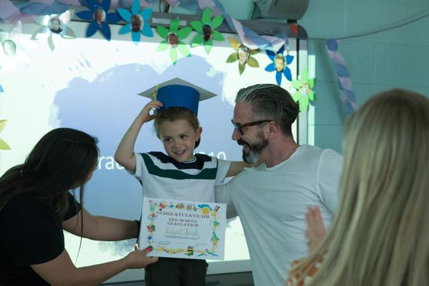 Riley graduating from pre-school in front of his proud father