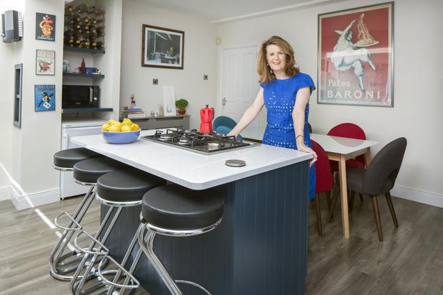 Author Christine Dwyer Hickey in her colourful kitchen. There's a lot of wine on the rack, but Christine herself doesn't drink, she is a great party giver. Not in the shot is the essential bookcase, full of poetry books.