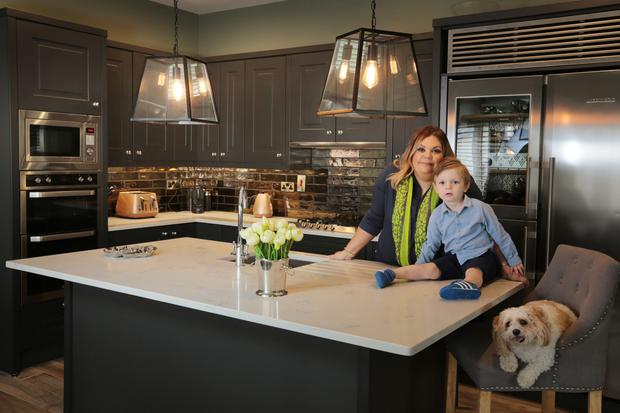 Lynn Pitcher, owner of Source Interiors, Swords, in her kitchen with her son, Shay, and her dog, Susie. The units are covered in an anthracite shade.