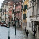 Changing: People walk in a flooded street during a period of seasonal high water in Venice last Sunday. Photo: Manuel Silvestri/Reuters