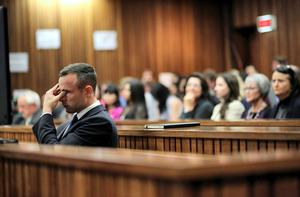 Oscar Pistorius rubs his eye in court in Pretoria after earlier questioning by state prosecutor Gerrie Nel.