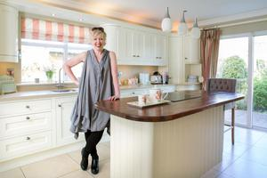 Interior designer Anne Marie Hamill in her kitchen, consisting of hand-painted units made by AJ Carpentry. Anne Marie does a cooking marathon every Sunday night, and her three daughters sit around the island for chats as she cooks.