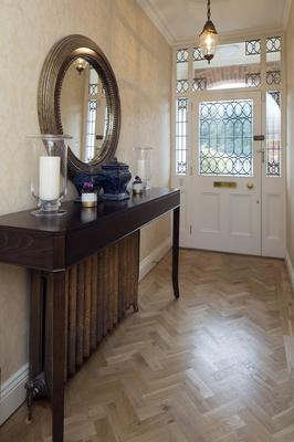 The blonde parquet flooring along with the feature glass in the door enhance the feel of a light-filled hallway. The table is from Helen Turkington