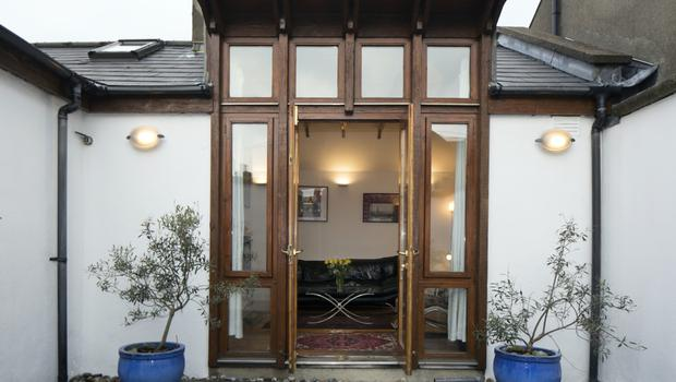 The living room and courtyard are linked with this extra-high set of  glass double doors