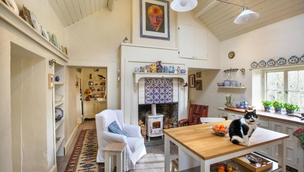 Deirdre recently created this airy, roomy space by removing the bedroom above and opening the whole area up to the roof. Most of the pottery lining the shelves is handpainted by Deirdre. The mantlepiece came from a dump in Scotland. She called this cat Neeps in honour of their Scottish ties