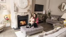 Fashion and interiors stylist Nikki Cummins Black in her living room with her adorable toddler, Indie Belle. Nikki put in the mantlepiece which she found online. The white feathered circle above it is a ceremonial headdress from Cameroon
