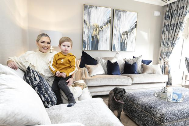 """Erin with her three-and-a-half-year-old son Harry in her cream and navy sitting room. The herringbone floors here and throughout the house are from Matt Britton. She has had her schnoodle, Pixie, for 10 years. """"She's half poodle and half schnauzer. I got her when my auntie passed away, on my auntie's birthday. I think she was sent to me at a special time, she's a great influence around the house, very calming,"""" she says. Photo: David Conachy"""