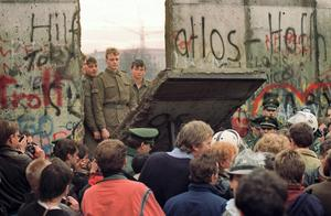 New dawn: West Berliners crowd in front of the Berlin Wall as they watch East German border guards demolishing a section to open a new crossing point between East and West Berlin, near the Potsdamer Square, on November 11, 1989