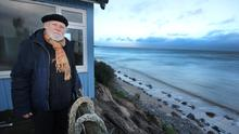 Teetering on the brink: Roddy Hickson at his abandoned home (right) overlooking Donaghmore beach in Co Wexford