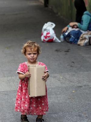 A Syrian refugee child begs for money on a street in the Lebanese capital, Beirut