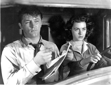 THIS WAY: Mitchum consulting a map, something most men are loath to do, in 'Where Danger Lies' with Faith Domergue