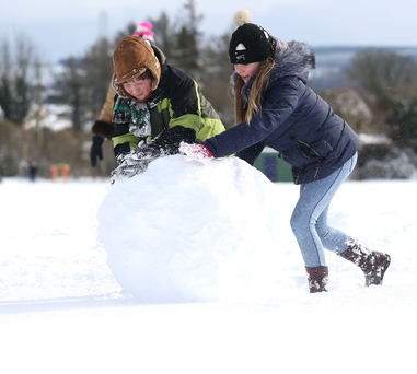Gotta roll with it: Alex Williams (10) and Sophia Kyryk(10) from Rathcoole, Co Dublin, play in the snow yesterday. Photo: Damien Eagers