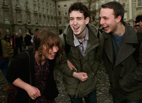 Brigid Francis-Devine, from Cork, (left) and Neil Murphy (centre) celebrate with Conor Burke a Law student, after receiving scholarships Brian Lawless/PA Wire