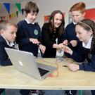 Tech savvy: Ciara Brennan shows her fifth class students at St Peter's primary School in Bray, Co Wicklow - from left, Kayden Clucas (10), Dominik Bessler (10), Dylan Fitzpatrick (11), and Shannon Hopewell (10) - how to code