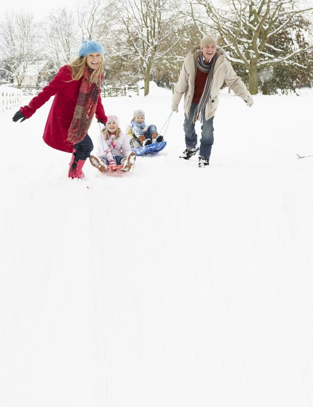 Mother And Father Pulling Children On Sledge